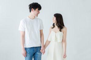 手をつないで見つめ合うカップル
