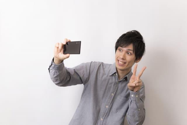 スマホで自分の顔を自撮りする男性